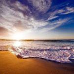 夕焼けと青い空と海を浜辺から撮った写真