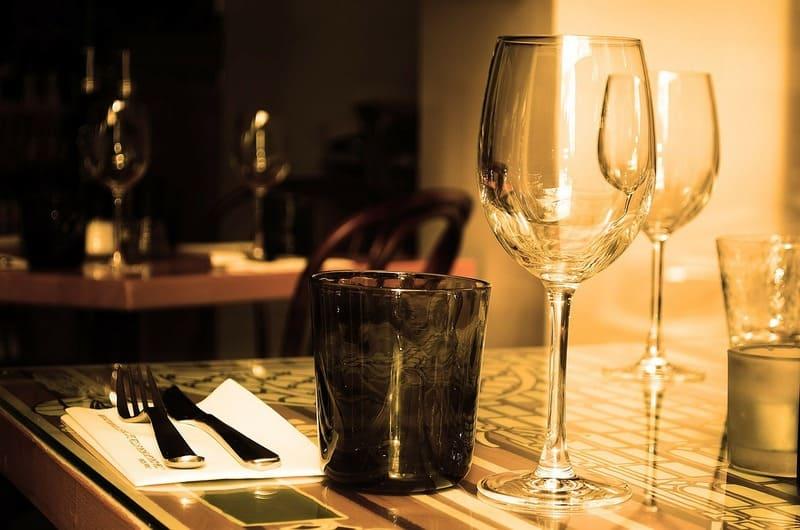 薄暗い室内で撮られたディナー用のワイングラスと食器の写真