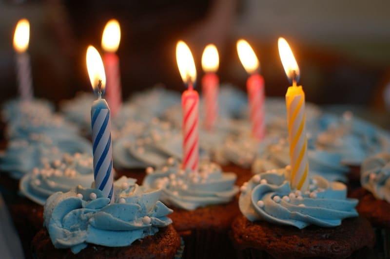ケーキに火のついたろうそくが何本も刺さっている写真