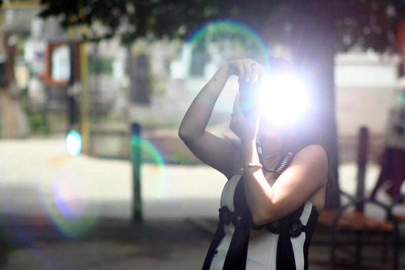 カメラのフラッシュを使って撮影している女性