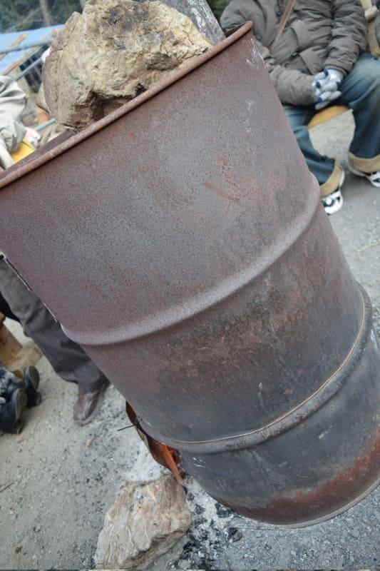 ドラム缶の薪ストーブと周囲に置かれているイス