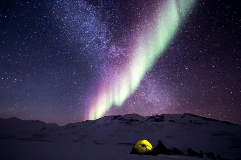雪山に張られたテントと星空とオーロラの写真