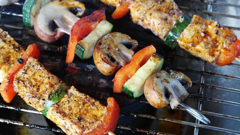 BBQでつくられた野菜とキノコと肉の串の写真