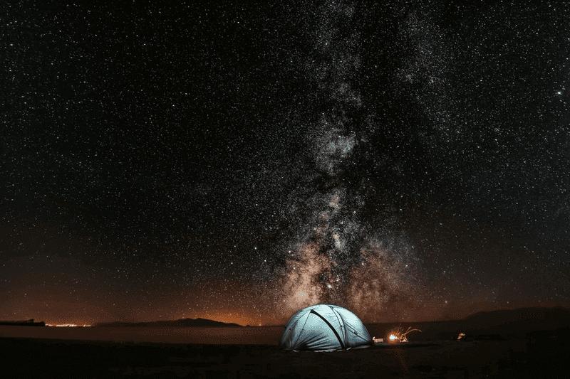 キャンプ場に張られたテントと天の川の写真