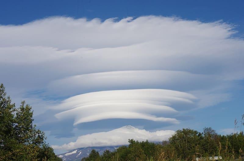 レンズ雲が何重にも重なっていて山の上を覆っており上部がケルビン・ヘルムホルツ不安定性雲となっている雲の写真