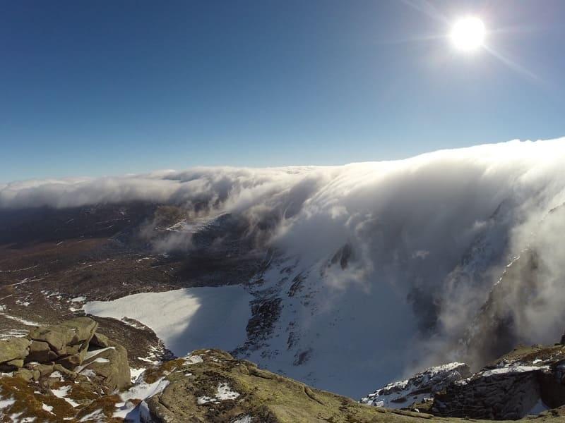 山から滝のように雲が流れ落ちている滝雲の写真