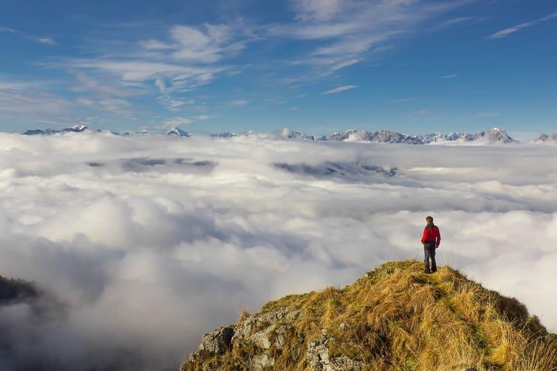 雲海と山頂から雲海を見下ろしている男性の写真