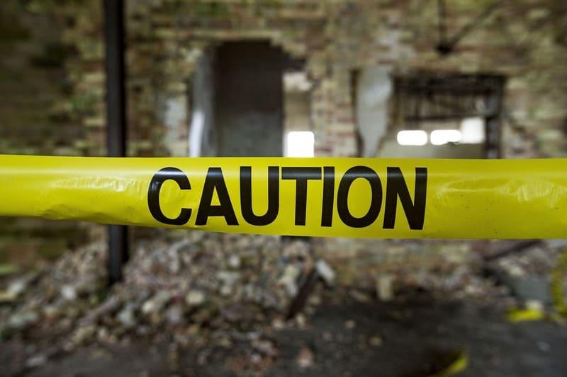 崩れかけた建物の前に張られている注意と書かれたビニールテープ