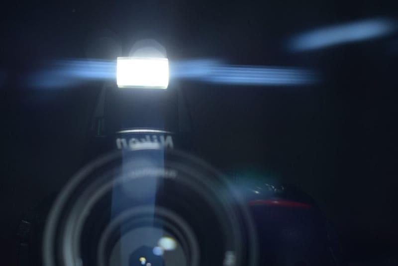 鏡に映ったフラッシュを光らせたニコンのカメラ