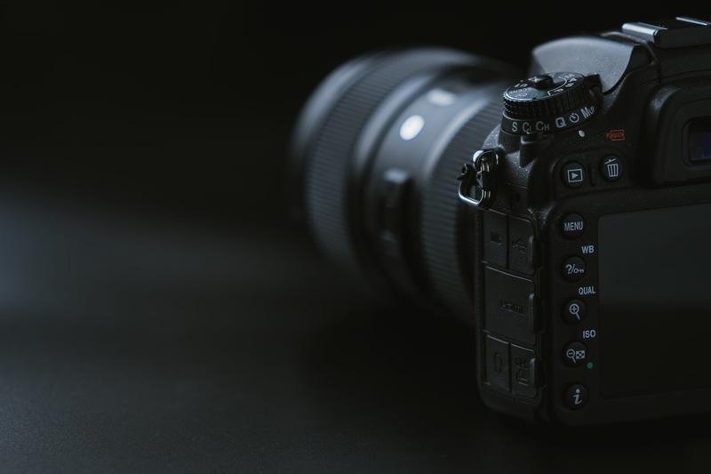 黒いテーブルの上に置かれた一眼レフカメラ