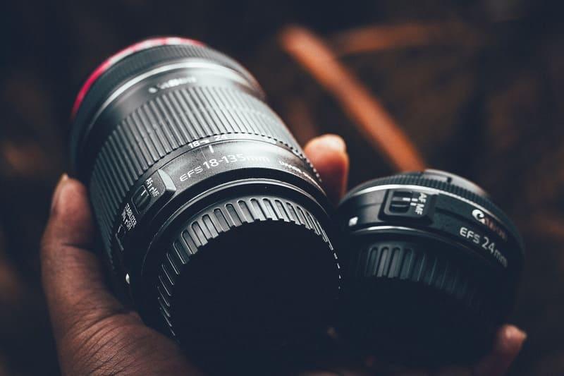 望遠レンズと標準レンズを手に持ったおじいさんの写真