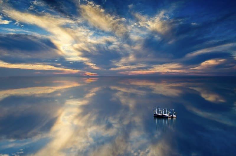 朝焼けに照らされた湖畔に反射する青い空と雲と船