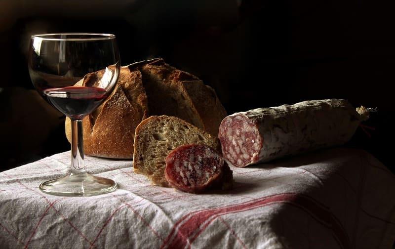 窓越しに太陽光が当たっている室内に置かれたワインとパンとサラミの写真