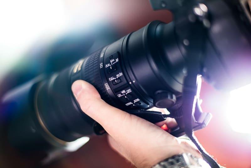 フードを取り付けた望遠レンズを持っている写真