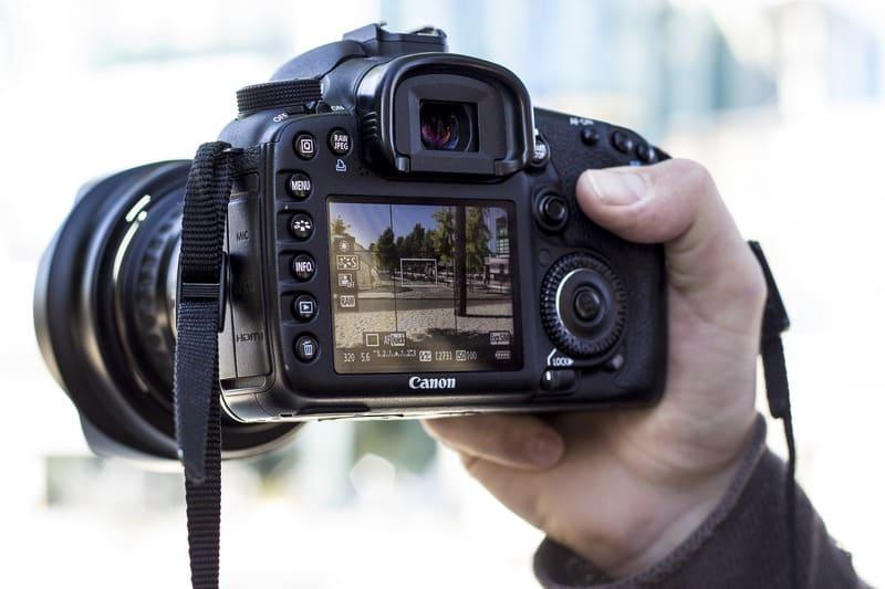 ライブビューモードで撮影しようとしている男性と一眼レフの写真