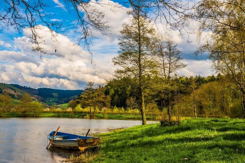 山や自然に囲まれた川に浮かぶボートと青い空に浮かぶ真っ白な綿雲
