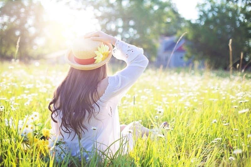 草原に座る帽子をかぶった女性を逆光で撮った写真