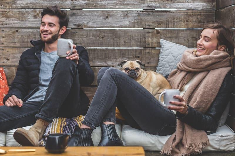 若い男性と女性と犬がソファに座って談笑している写真