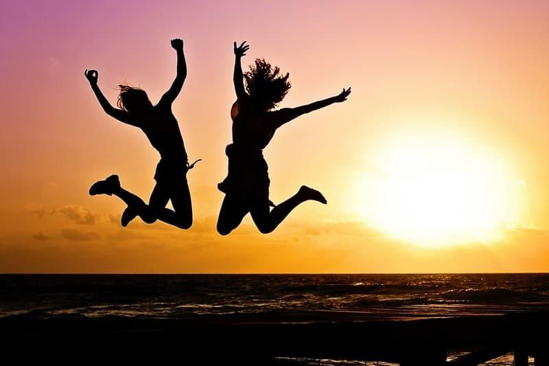 夕焼けに照らされた浜辺で二人がジャンプしているシルエット写真