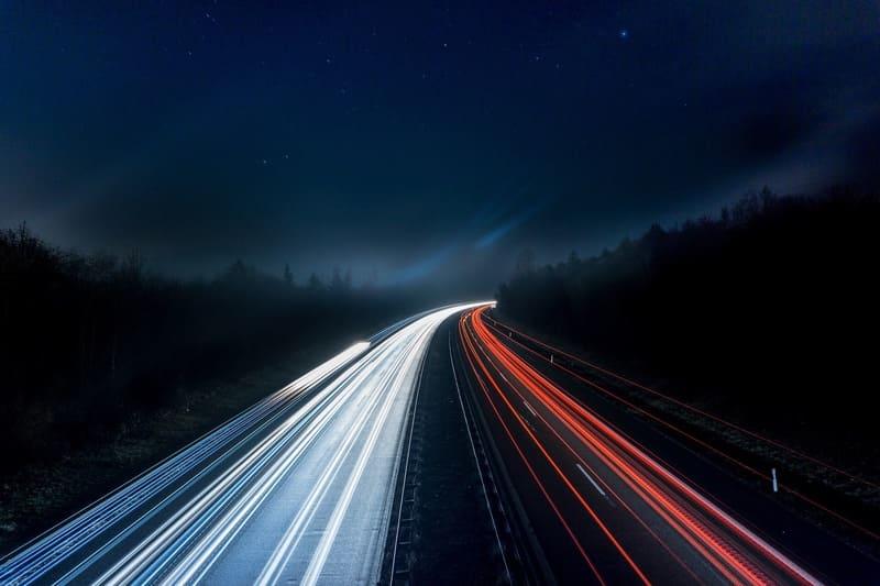田舎の道路で長時間露出撮影で車の光跡が残っている写真