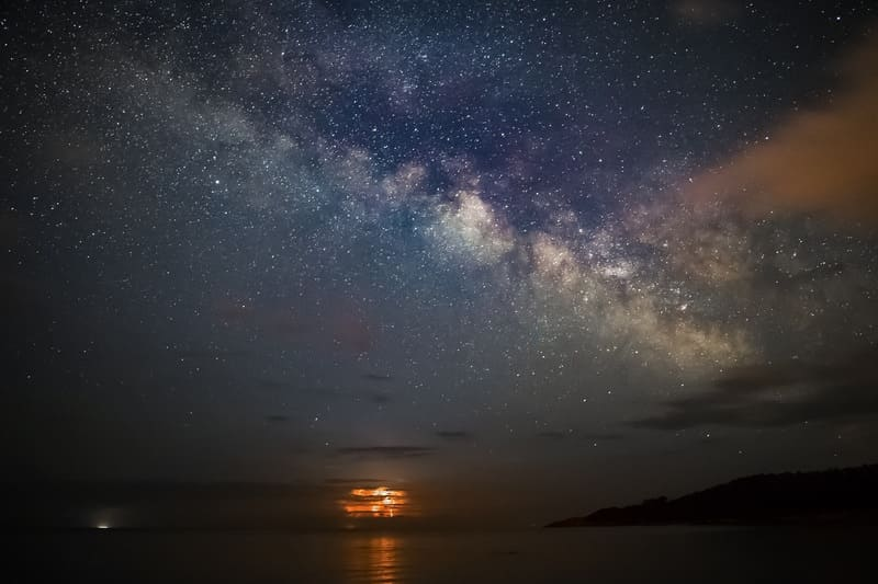 海辺で撮られた天の川とうっすら浮かぶ夕焼けの写真