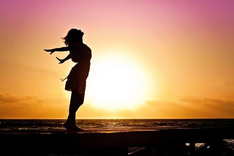 夕焼けと海をバックに両手を広げて立っている女性のシルエット