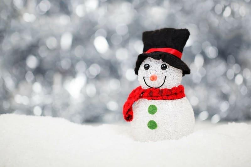 帽子とマフラーを付けた雪だるまの後ろに降る大雪
