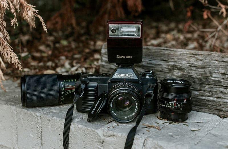 屋外で撮られた外付けフラッシュを取り付けたデジタルカメラと交換用レンズの写真