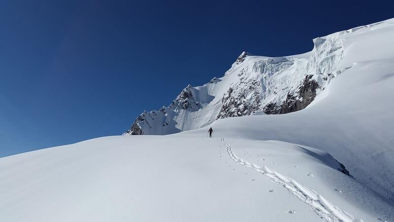 天気がよく青空広がる雪山で撮られた登山している人の写真