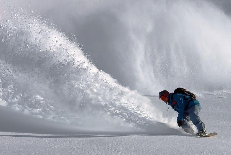 スノーボードでターンをして雪を巻き上げている人の写真