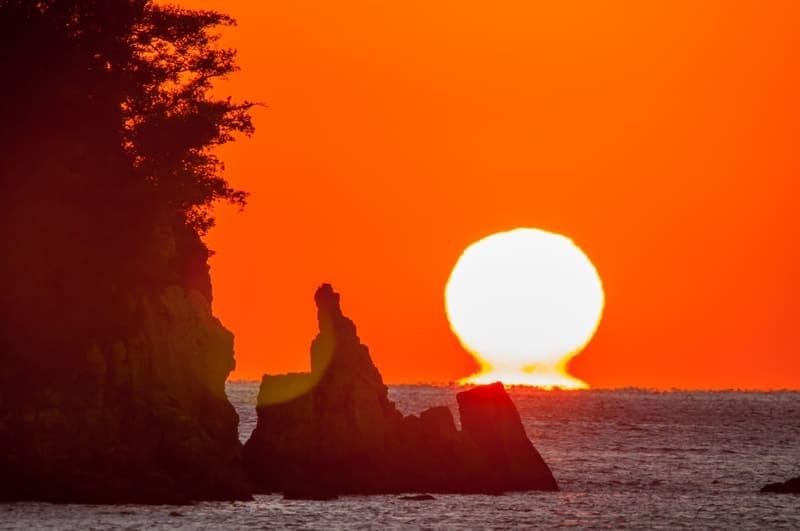 水平線に浮かぶだるま太陽の写真