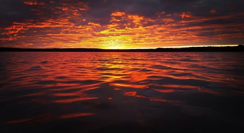 オレンジ色に輝く海に反射する夕焼けの写真