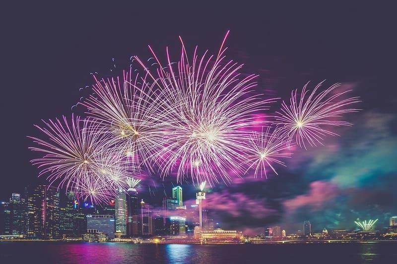 都会の上空に打ち上げられたピンク色の花火の写真