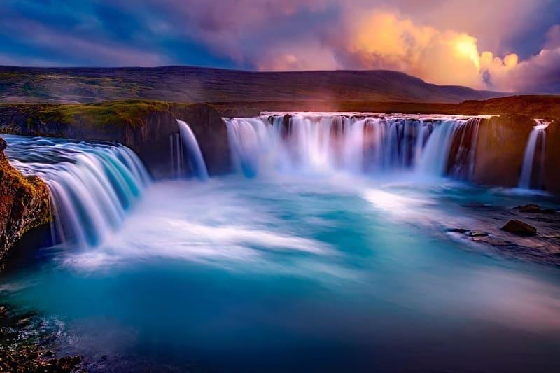 夕焼けに照らされた長時間露出撮影された滝の写真