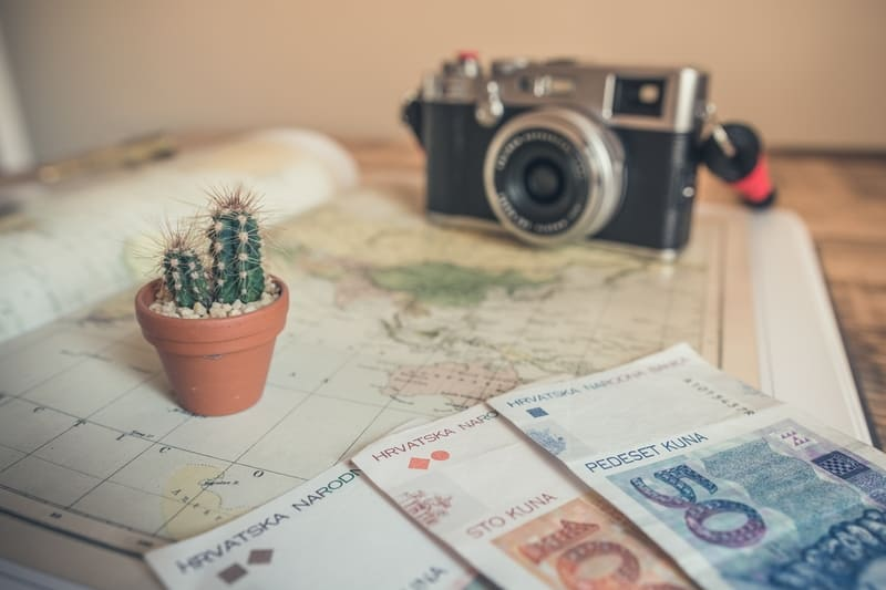 机の上に置かれたカメラとお金の写真