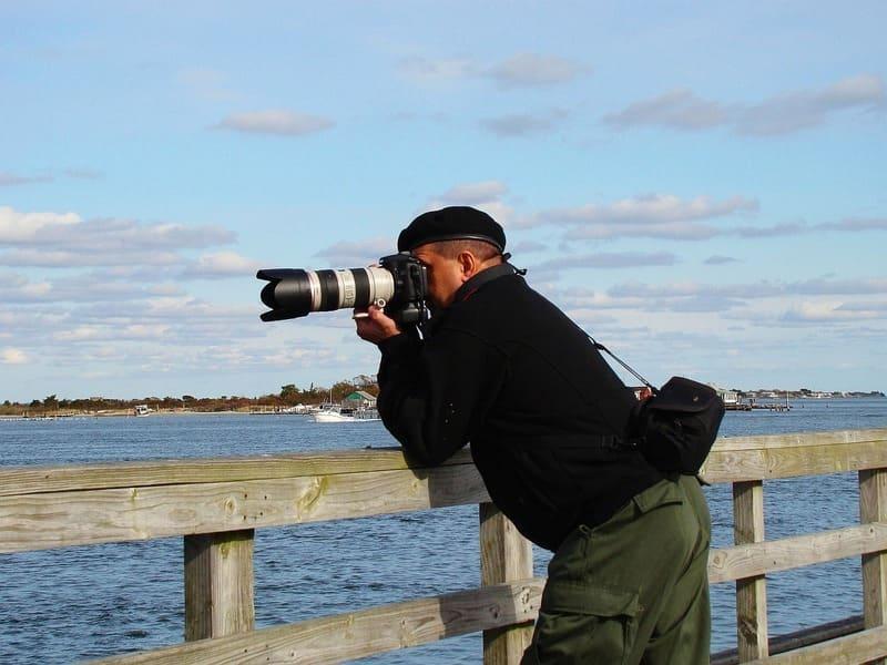 柵に肘を当てて望遠レンズで撮影している人