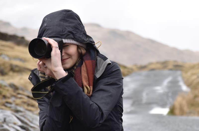 脇を締めてカメラを縦に持っている女性