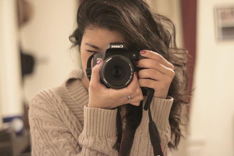 鏡に向かってカメラを構える若い女性