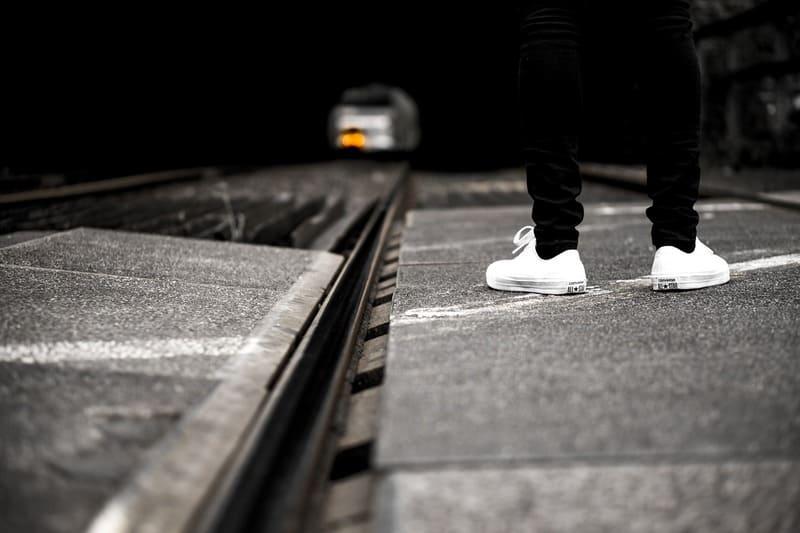 線路の隣に立っている男性の足の写真