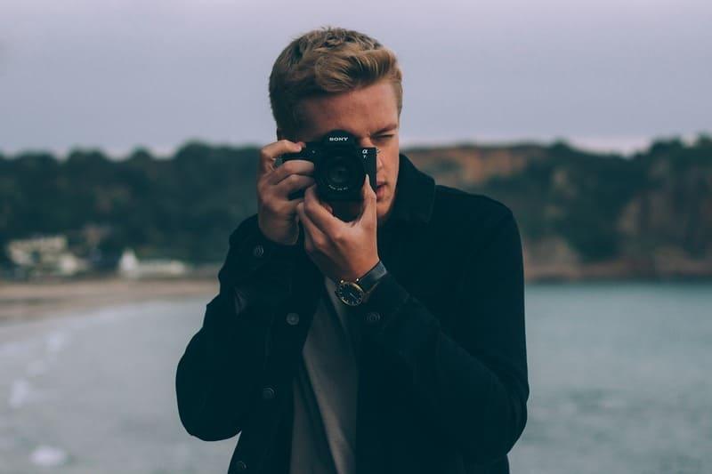 カメラに向かってカメラを構えている男性