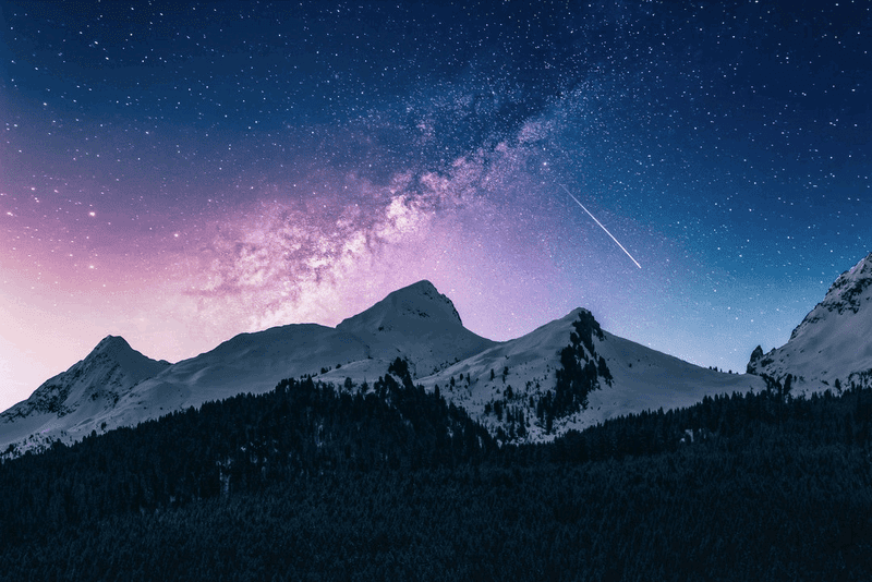 雪山の上空に広がる天の川と流れ星の写真