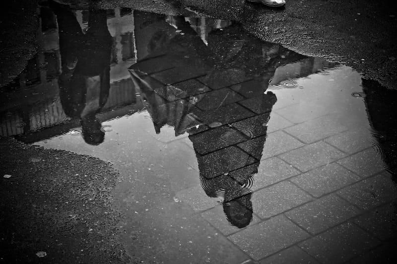 モノクロの水たまりに写った人の写真