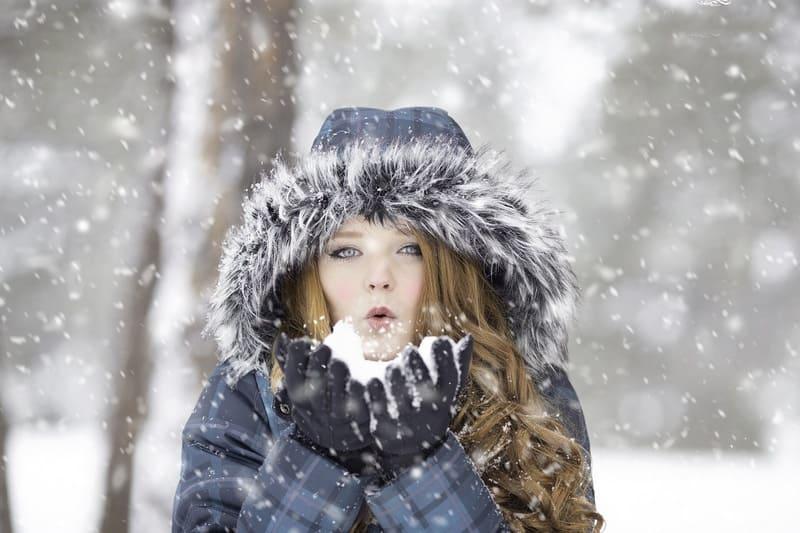 手にもった雪を吹いている女性