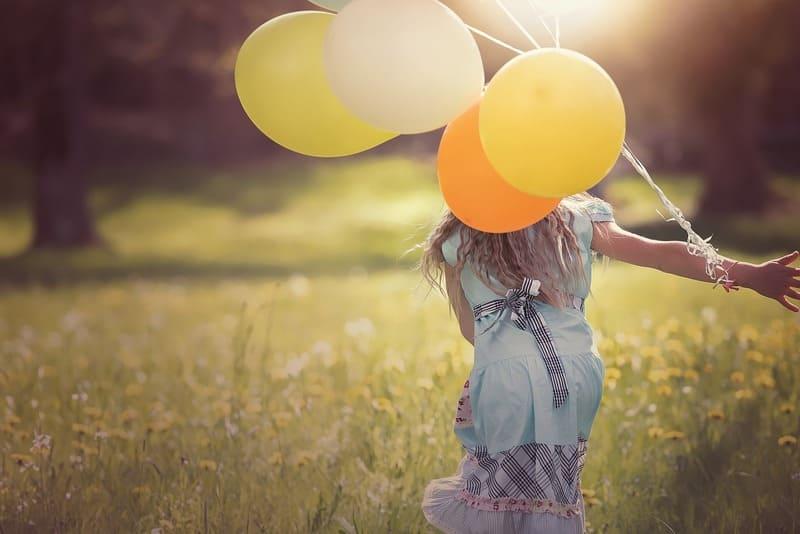 草原をかける風船を持った女の子