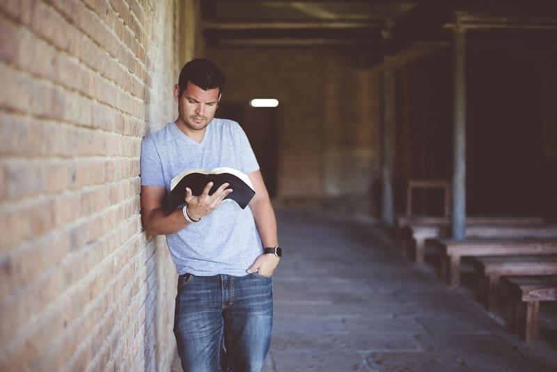 壁にもたれた本を読んでる男性
