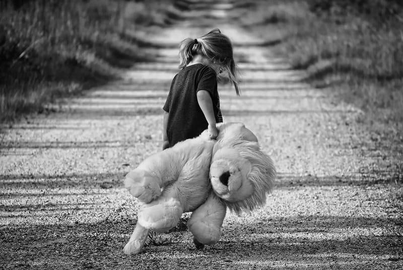 大きいぬいぐるみを持った女の子のモノクロ写真