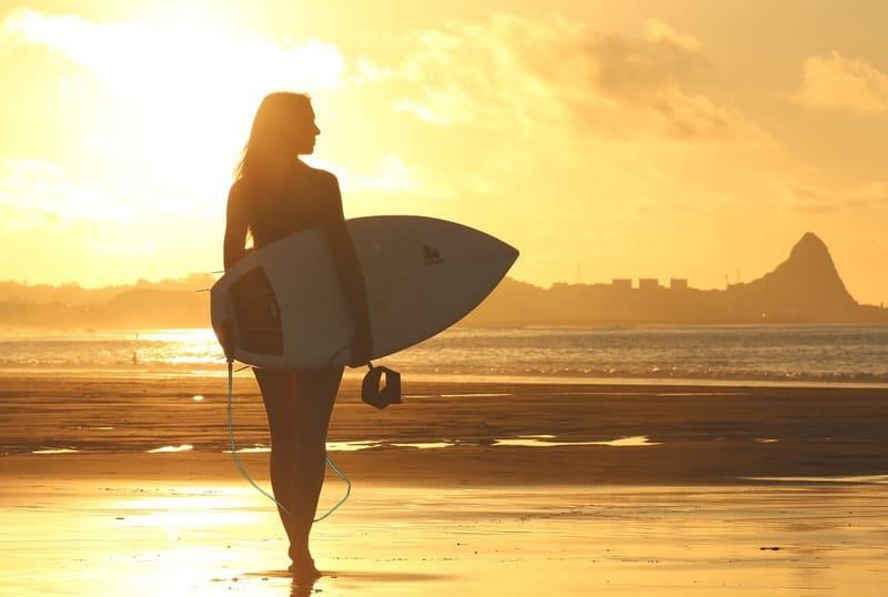 サーフボードを持った夕方の浜辺を歩く女性