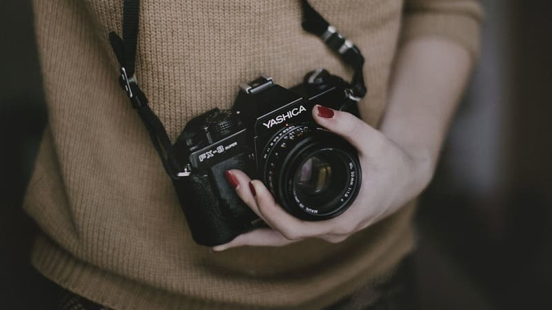単焦点レンズを付けたカメラを持った女性の写真