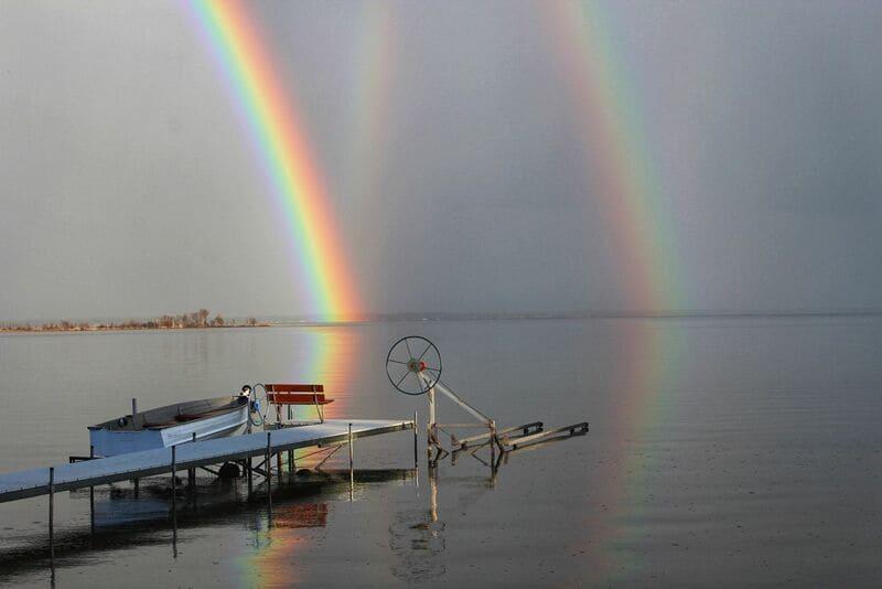 副虹と反射虹がうっすらと浮かぶ海辺の虹