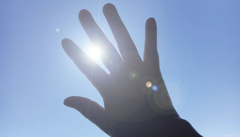 太陽を手で隠している写真